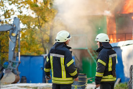 two firefighters stand back on a fire, on the background of the fire Stok Fotoğraf