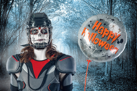 Happy halloween. hockey player in a hockey helmet and mask with a balloon against the backdrop or background of scary forest. holiday halloween. All Saints Day