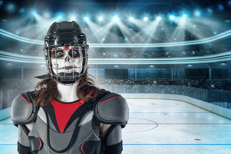 Happy halloween. hockey player in a hockey helmet and mask with a balloon against the backdrop or background of a hockey field. holiday halloween. All Saints Day Фото со стока