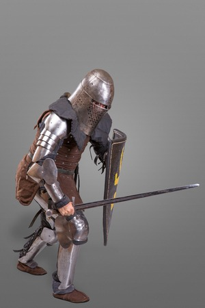 knight in breaths in a helmet with a sword and shield in battle isolated over grey background
