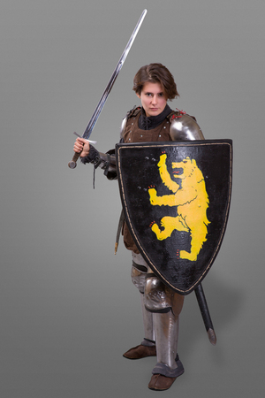 Girl in armor with a sword knight wuth shield isolated over grey background Reklamní fotografie