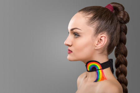 Portrait of brunette woman with long pigtail. decoration on the neck in the form of a rainbow isolated over grey background. space for text