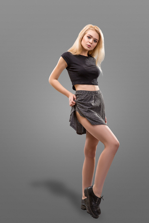 Fashion model dressed in short gray skirt isolated over grey background