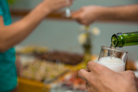 Pouring champagne into glass at hen-party, close up. restaurant feed. New Year Christmas