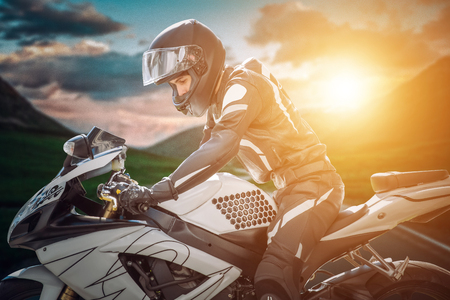 Motorcyclist on sport bike stands on the edge of the mountains in the background of a bright sunset. Stockfoto