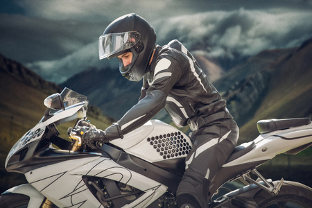 Rider on a motorcycle with Chief Mountain as the background. mountains of a cloud. motorcyclist in helmet on motorcycle