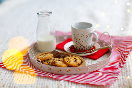 Glass with milk and oatmeal cookies with chocolate chips close-up on white tray. New year lights and bokeh Stock Photo