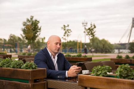 people, technology, leisure and lifestyle - bald man with smartphone texting message at city street cafe