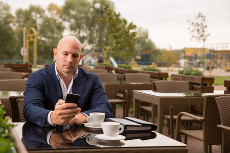 business, technology and people concept - bald man with smartphone and coffee cup texting at city street cafe