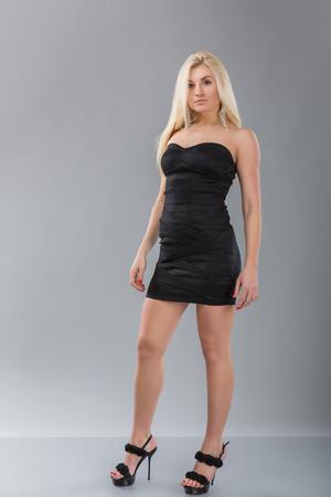 Young woman girl in black dress studio portrait. Blonde hair model female in black short dress over gray background Standard-Bild