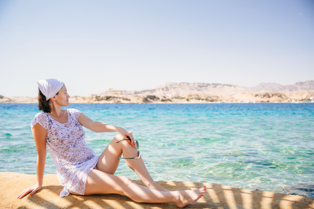 a woman dressed in a white tunic is seating in front the sea, she is watching an island. Sharm El Sheikh. Space for text