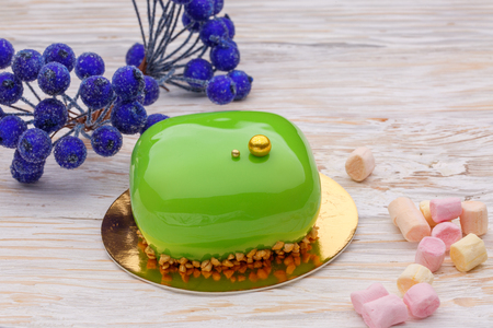 Still life green mousse cake with marshmallow over white wooden background und blue sugar berries. Sweet Stock Photo