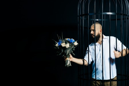 bearded man holding out a bouquet with flowers. The brutal man in the cage over black background. Stodio shot. Space for text Banco de Imagens