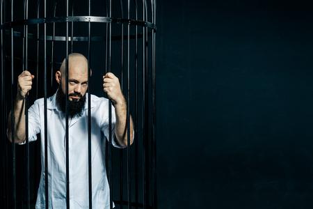 Depressed male inmate holds prison bars in despair. Fashion concept over black background. Copyspace Archivio Fotografico