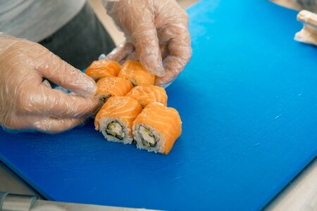 Chef hands putting sushi. Cook in gloves placing delicious sushi rolls on black plate. cookery