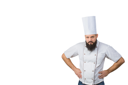 Portrait of handsome evil bearded male chef in uniform hands on waist isolated on white background, copy space on side. Stock Photo
