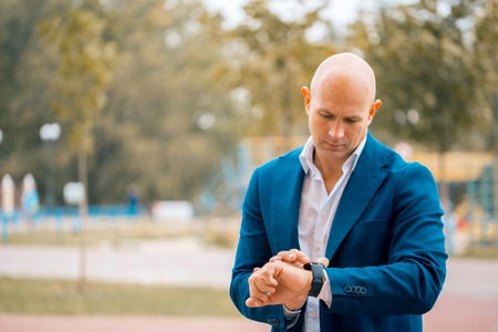 Serious male bald entrepreneur in formal suit looking at wristwatch planning working schedule , confident executive manager checking time while waiting for meeting standing outdoors