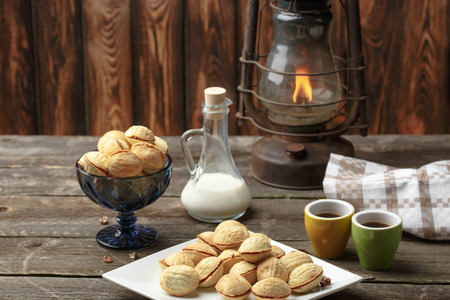 delicious walnut shaped shortbread sandwich cookies filled with sweet condensed milk and chopped pistachio nuts. against the background of the ingredients, view from above, close-up Stock Photo