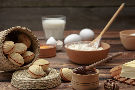 homemade cookies shaped nuts with cream boiled condensed milk on wooden table. The ingredients in the background. rural style. Cuntry style Stock Photo