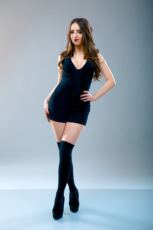 beautiful woman in a short black dress and knee socks or gaiters over grey background. Model test