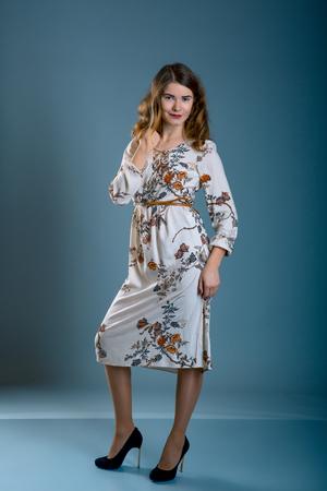 brunette in a flower print dress over grey blur background. Model test