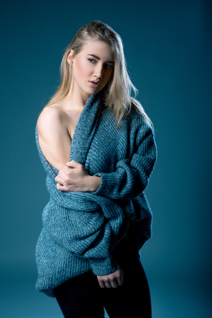 young blonde woman in a sweater with bared shoulder over dark background. Model test