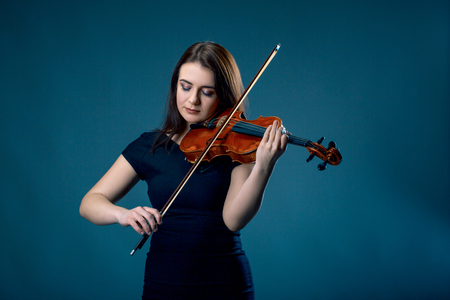 Woman with violin on blue grey background. Studio shoot