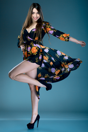 Young fashionable brunette woman in dress with floral print in high heels posing in studio on dark background. cruise collection
