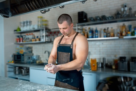 bodybuilder chef in hotel or restaurant kitchen interior knead the dough on the table. Pizza cooking. cooking process