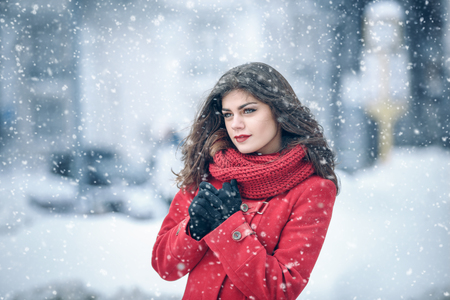 Winter. Girl brunette capless smiles on the background of snow. Close-up. hair develops. wind and snow 版權商用圖片 - 97614572