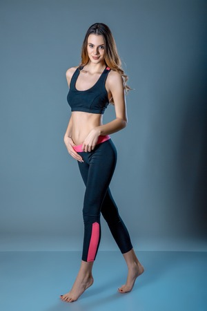 Fitness young pretty woman in black leggings and tank top posing with hands on hips. Full body length portrait on blue grey studio background. Sport concept