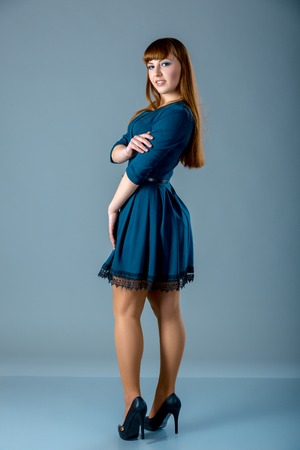 Portrait of a plus size female redhead model posing in blue dress over gray background. Beautiful woman with curvy figure. Banque d'images