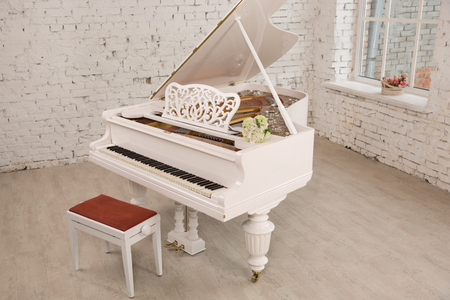 white grand piano standing in elegant white interior of Brick walls