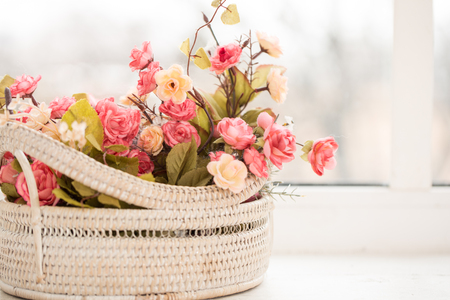 colorful roses and flowers in a basket on window-sill