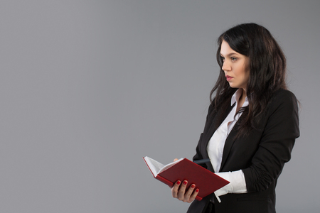 Young business woman writing down notes to notepad. Pretty thoughtful business lady writing on clipboard standing over gray studio background with copy space. Stock Photo