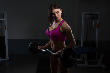 beautiful girl is engaged in the gym. Halthy concept with vulture or dumbbell. Fitness on dark background Stock Photo