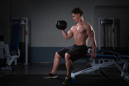 handsome young man in shorts, doing exercises for biceps, on a dark background in the studio. athlete with dumbbells at the gym on dark Stock Photo