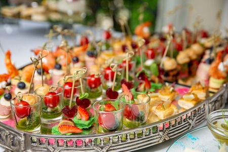 Light snacks, canap s with lard, cheese, meat, sauce, cherry tomatoes. Snacks for parties or reception