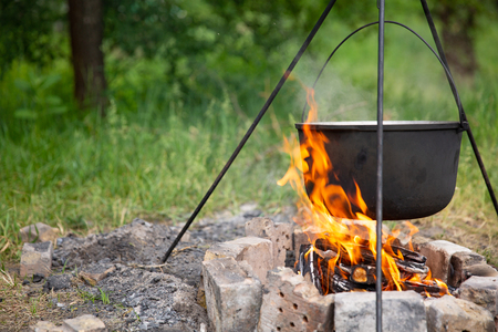 Cooking in a cauldron at the stake. the food is cooked in a cauldron at the stake in the open air
