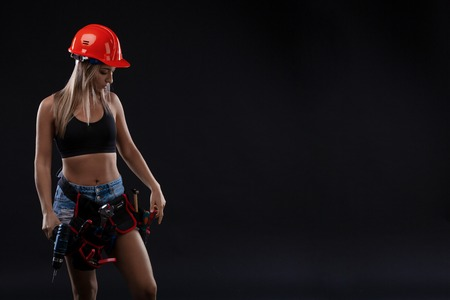 attractive sexy girl in safety helmet with tool belt holding electric drill on black background. Copy space. a woman with a male profession. Sex equality and feminism.