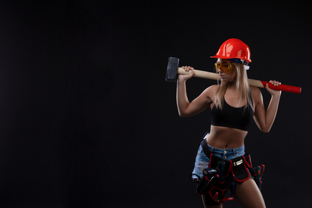 Sex equality and feminism. Sexy girl in safety orange helmet orange holding hammer tool. Attractive woman working as construction worker. Copy Space. a woman with a male profession Stockfoto