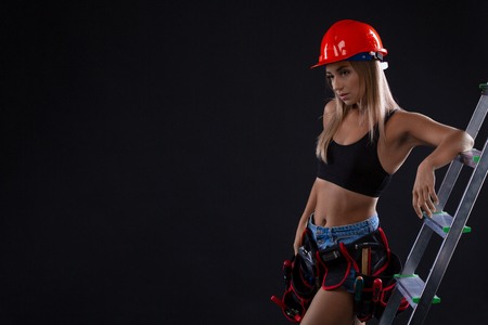Attractive young woman doing repairs at home. Portrait of a female construction worker. Building, repair concept. Feminism and Gender Equality. Copyspace