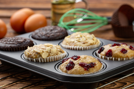 Different Muffins in bakeware or muffin pan on broun wooden background. Basic muffin recipe. Homemade muffins for breakfast or dessert. Ingredients