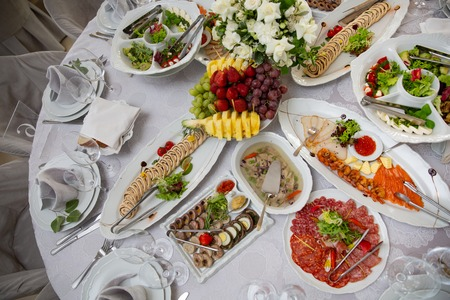 Buffet table of reception with cold snacks, meat, salads and fruits. Served table