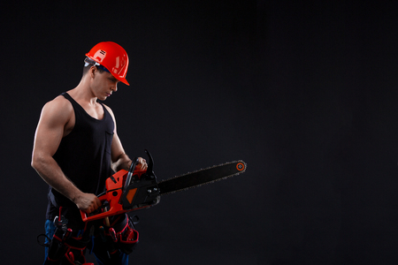 Chainsaw and young worker in the helmet. The naked man broke the chainsaw. Attractive guy with tool on black background. Builder or lumberjack, wood processing Stock Photo