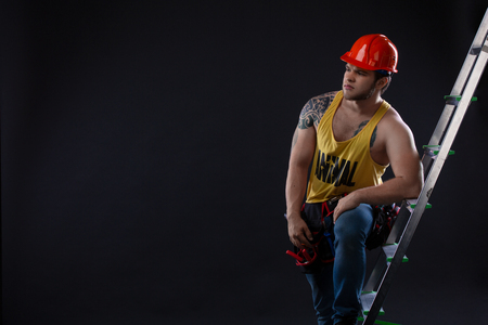 Portrait of handsome builder with construction ladder on black background Stock Photo