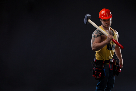 brutal Muscular worker man with a hammer. man in tattoos on a black background