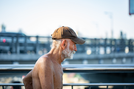 Fine art photo portrait of elderly man with wrinkled closeup face. sunburnt homeless man in a cap outdoor
