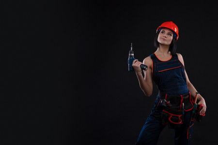 Attractive sexy young woman doing repairs at black background. Portrait of a female construction worker. Building, repair concept. Copy space