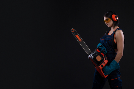 beautiful hot sexy woman hold a chainsaw over black background. Copy space Standard-Bild